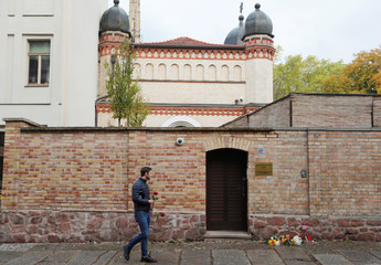 A man keeps flowers outside the synagogue in Halle