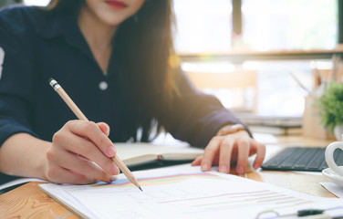 Closeup hand of young woman writing on paperwork with pencil while working with laptop at office desk.