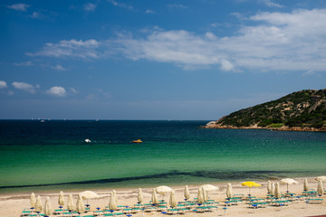 Costa Smeralda beach escape. Amazing beach views from Sardinia, Italy. Nobody on the beach. Closed umbrellas and sun chairs.