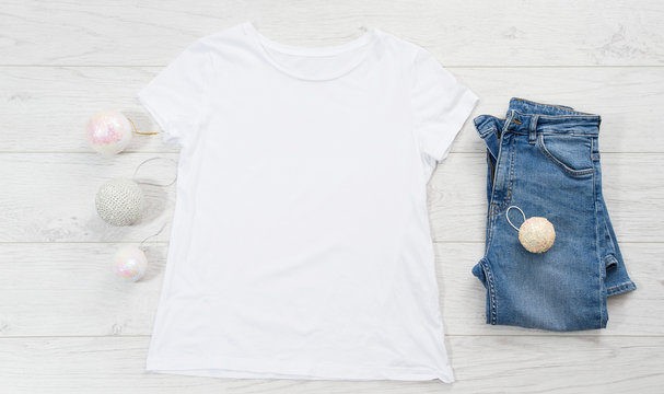Close up white blank template t shirt with copy space and Christmas Holiday concept. Top view mockup t-shirt and jeans on white wooden background. Happy New Year decorations accessories. Xmas outfit
