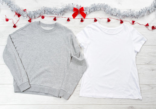 Close up white blank template t shirt, gray sweatshirt hoodie with copy space and Christmas Holiday concept. Top view mockup t-shirt, red bow on white wooden background. Happy New Year decorations