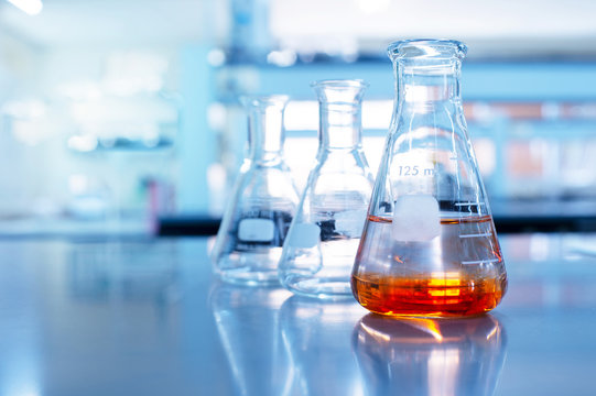 orange solution in science glass flask in blue chemistry school laboratory background