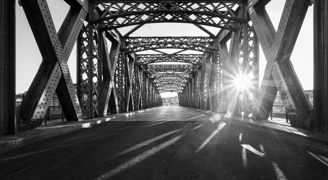Black and white asphalt road under the steel construction of a bridge in the city on a sunny day. Evening urban scene with the sunbeam in the tunnel. City life, transport and traffic concept.