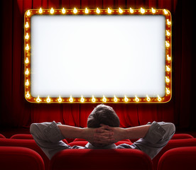 Man sitting in front of lighted sign on red theatre curtain