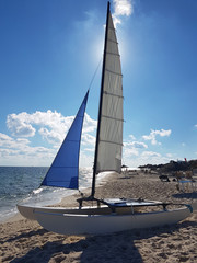 A sailing boat is placed on the sandy beach