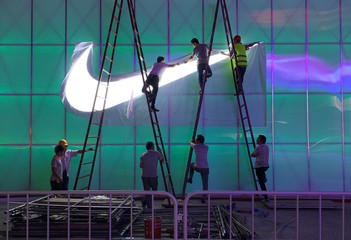 Workers install a Nike logo lamp outside the Wukesong Arena in Beijing