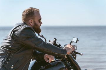 Side view of a handsome bearded biker posing while sitting on his motorcycle