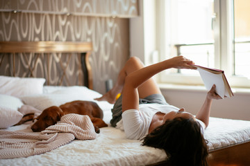 Young woman with dog  lying on bed while reading book