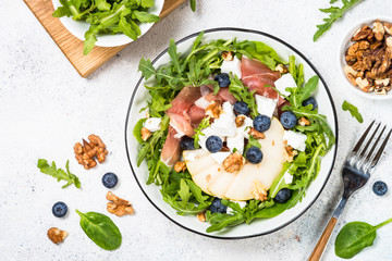 Green salad with leaves, fruit and jamon.