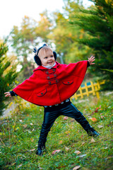 Little girl in the fall. Fashionable baby in a red coat for a walk.