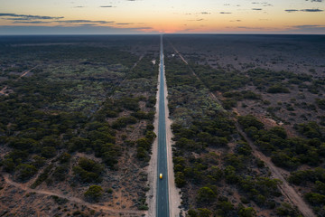 Aerial view at dusk of the long straight road that is the Eyre Highway, crossing the Nullarbor Plain in South Australia