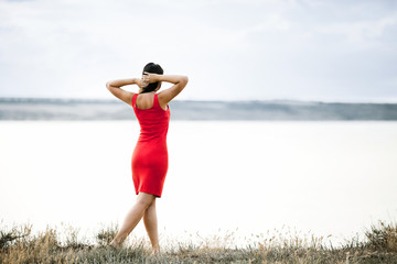 Back view of a girl dressed in a red dress, which is standing on the grass and looking on the beautiful lanscape with putting her hands on the hair