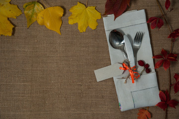 Composition for Thanksgiving. Invitation to dinner.  Spoon, fork, knife, linen napkin, autumn leaves on a textile background. Free space for your text.