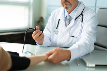 A doctor measures the blood pressure of a patient closeup photo
