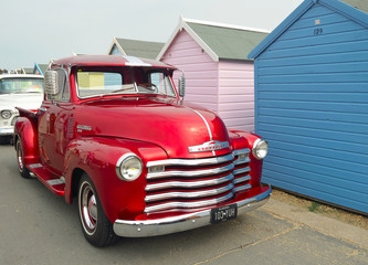 Classic Red  Chevrolet 3100 pickup truck on seafront promenade in front of beach huts.