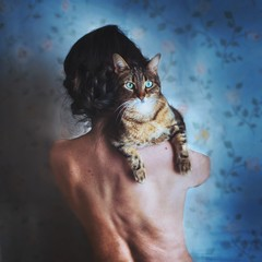 Rear view of woman carrying cat on her shoulder