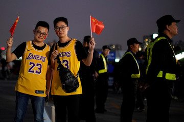 Fans in LeBron James jerseys pose for pictures with Chinese flags near security personnel outside the Mercedes-Benz Arena before the NBA exhibition game between Brooklyn Nets and Los Angeles Lakers in Shanghai