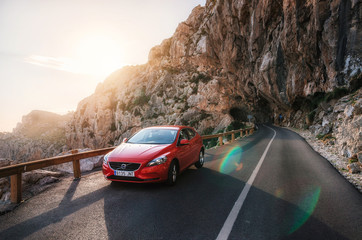 Red car Volvo V40 traveling on the mountain serpentine through a tunnel of a rock along the coast of Majorca against the sunshine. Roadtrip around Mallorca island