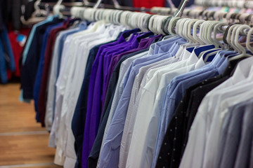 Many different colorful clothes on a hanging rack in the retail shop store. Soft selective focus photography