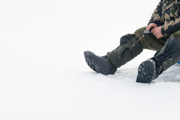 Winter fishing on ice. Man jiggling bait in an ice hole. Relaxing in the wild