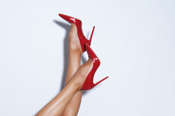 Isolated female legs in red high heels. Studio shoot. Wall mural