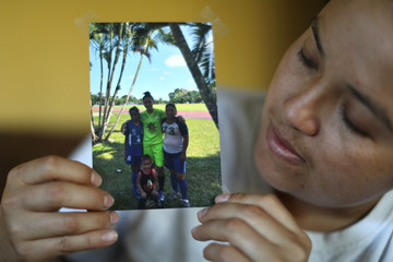 Guatemalan asylum-seeker Marveny Suchite shows a photo of her family, in Berkeley