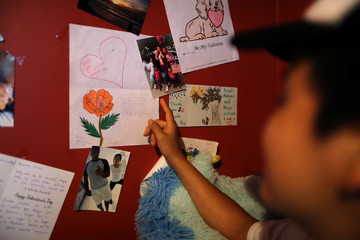 Guatemalan asylum-seeker Marveny Suchite displays photos of her family on the wall of the home in which she is staying in Berkeley