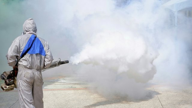 Rear view of  outdoor healthcare worker using fogging machine spraying chemical to eliminate mosquitoes and prevent dengue fever at general location in community