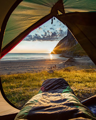 Tuinposter Kamperen Camping on the Beach at Sunset. Spectacular sunset view to rugged mountain peaks above Kvalvika - famous surfing beach at Lofoten islands, Norway. Lifestyle summer journey vacations