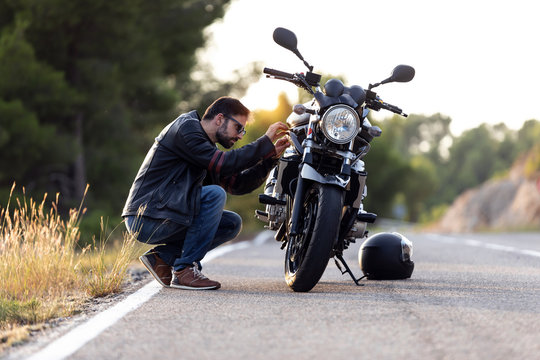 Young man biker checking his motorbike before driving it on the road.