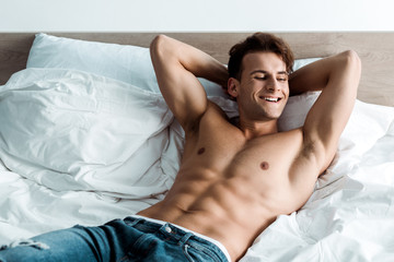 happy man in denim jeans lying on bed at home