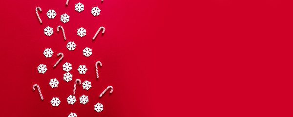 Christmas New Year design concept with white snowflakes with many candy cane on pastel red background on a red background.