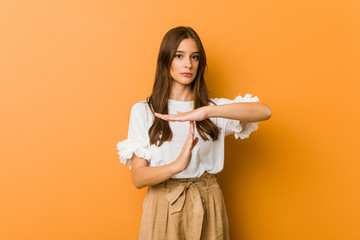 Young caucasian woman showing a timeout gesture.