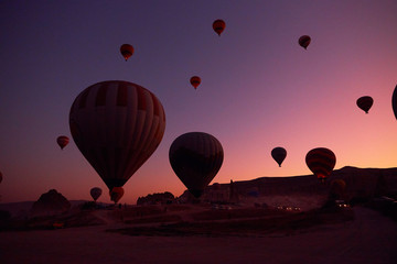 sunrise photo with big air balloons in the sky and people and cars on the ground