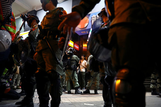 A man is questioned by the riot police at the Harbour city in Tsim Sha Tsui district, in Hong Kong