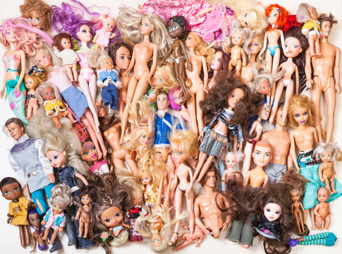 MOSCOW, RUSSIA - JUNE 17, 2019: top view of various used fashion dolls ( Barbie, Ken, Shelly, Chelsea, Kelly, Bratz, Moxie, My Scene, Winx, Witch, etc) on gray conrete board.