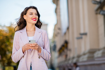Fototapete - Portrait of her she nice-looking attractive lovely charming pretty shine winsome cheerful cheery wavy-haired girl red lips spending free time using cell app 5g service in downtown outdoors