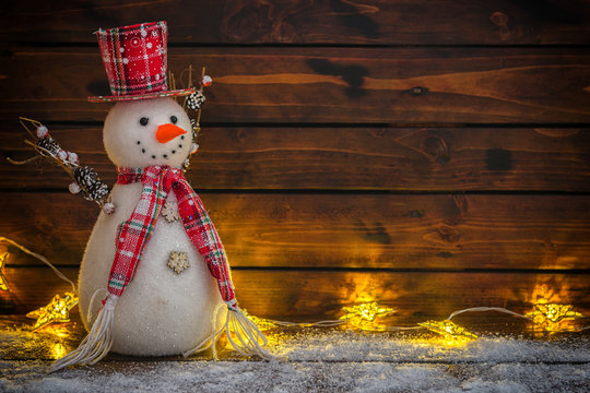 Christmas background with Christmas lights and snowman on the old wooden board
