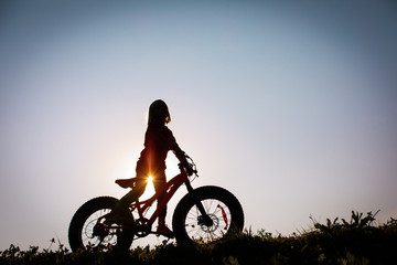 happy girl riding bike at sunset, active kids