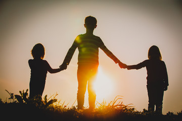 silhouettes of kids - boy and girls - holding hands at sunset