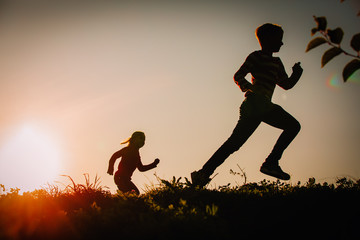 Silhouette of happy boy and girl running at sunset