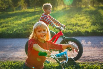 happy girl and boy riding bikes in sunset nature
