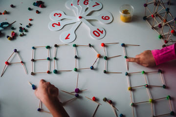 kids making letters and geometric shapes from clay and sticks, engineering and STEM
