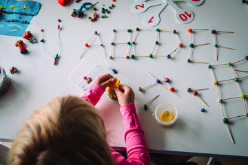 girl making letters, geometric shapes from sticks and clay, engineering and STEM