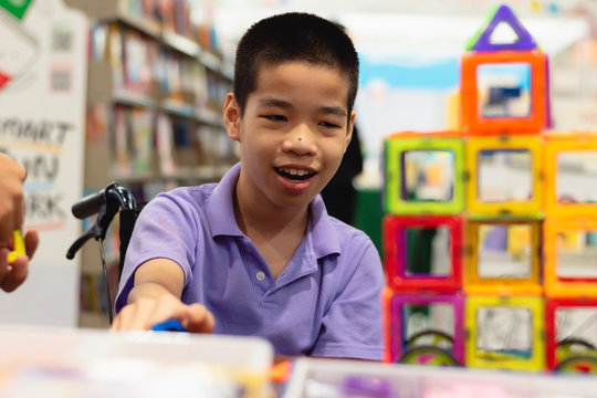 Disabled child on wheelchair is interested in skills development toys in Books and toys fair,Special children's lifestyle,Life in the education age of special need kids,Happy disability kid concept.