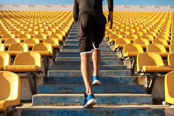 Close up back view of sportsman running among empty stadium seats