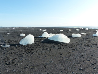 Diamond Beach, here, the icebergs which fill Jökulsárlón glacier lagoon wash up on shore, standing dazzling and defiant in stark contrast to the black sand beach. South Coast of Iceland.