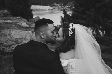 Black and white wedding photo of loving Kazakh Asian couple in nature, beautiful bride in dress and veil and groom in suit hug and kiss