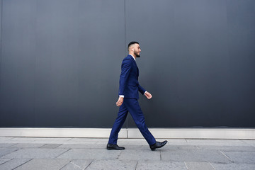 Asian Kazakh businessman walks along the black wall