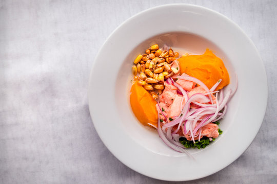 Delicious and fresh ceviche served with onions, sweet potato, toasted corn and lettuce. Latin food. White background. Top view